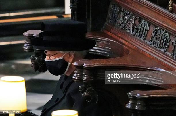 Britain's Queen Elizabeth II sits alone in the quire of St George's Chapel during the funeral service of her husband Britain's Prince Philip, Duke of...