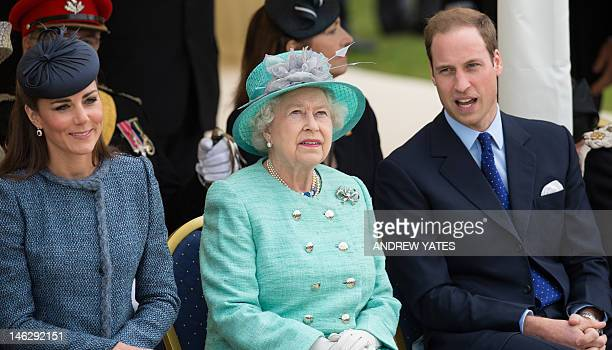 Britain's Queen Elizabeth II sits flannked by Catherine Duchess of Cambridge and Prince William during a visit to Vernon Park in Nottingham central...