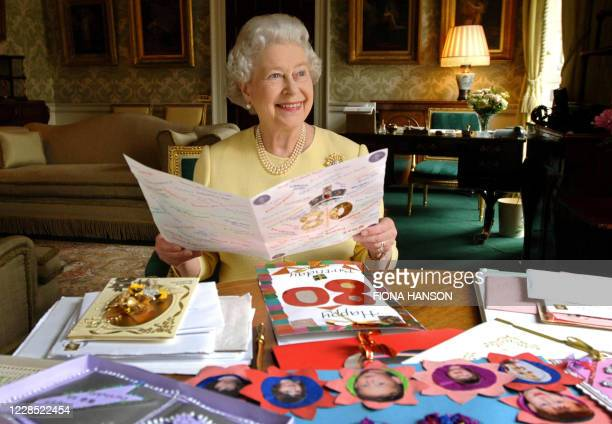 Britain's Queen Elizabeth II sits in the Regency Room at Buckingham Palace in London 19 April 2006 as she looks at some of the cards which have been...