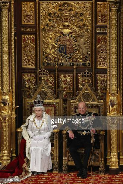Britain's Queen Elizabeth II sits on the throne next to Prince Philip, Duke of Edinburgh in the Chamber of the House of Lords as she waits to read...