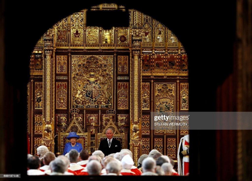 TOPSHOT - Britain's Queen Elizabeth II sits slongside her son Britain's Prince Charles, Prince of Walesr during the State Opening of Parliament in the Houses of Parliament in London on June 21, 2017. - Queen Elizabeth II will formally open parliament and announce the British government's legislative programme on Wednesday, two days later than planned. The state opening, a ceremony full of pomp in which the monarch reads out the Queen's Speech detailing the government's programme for the coming year, was due to take place on June 19, but was delayed after Britain's Prime Minister Theresa May's Conservative party lost their majority in the House of Commons in the June 8 election.