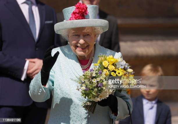 Britain's Queen Elizabeth II smiles and waves to members of the public as she leaves after attending the Easter Mattins Service at St. George's...