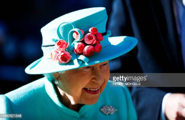 TOPSHOT Britain's Queen Elizabeth II smiles as she arrives at The Lexicon shopping centre during a visit to Bracknell west of London on October 19...