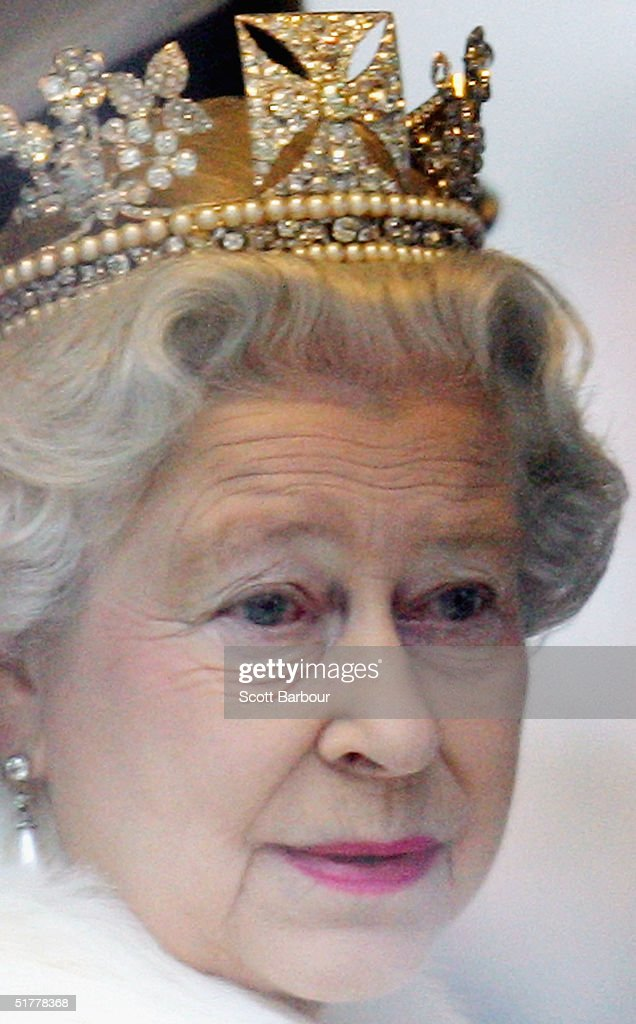 Britain's Queen Elizabeth II smiles as she looks out of the window of her horse drawn carriage as she leaves the Houses of Parliament after delivering her annual speech at the State Opening of Parliament November 23, 2004 in London, England.
