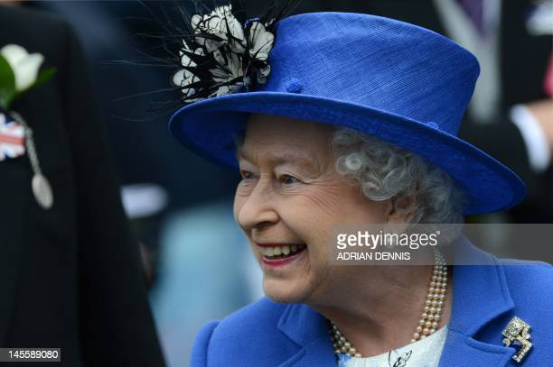 Britain's Queen Elizabeth II smiles as she talks to a racegoer at the parade ring before the Diamond Jubilee Coronation Cup on Derby Day the second...