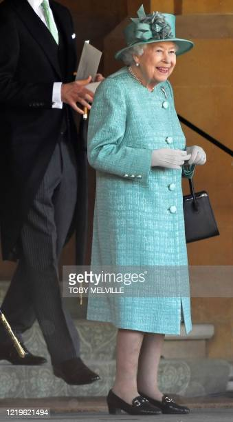 Britain's Queen Elizabeth II smiles towards the end of a ceremony to mark her official birthday at Windsor Castle in Windsor, southeast England on...