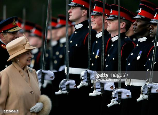Britain's Queen Elizabeth II smiles with her grandson Prince Harry during the Sovereign's Parade at the Royal Military Academy in Sandhurst, southern...