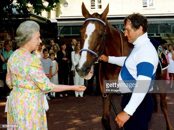 Britain's Queen Elizabeth II speaks to veteran jockey Bob Champion as Grand National winner Aldaniti turns down a slice of carrot offered to him by...