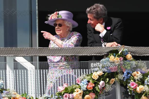 Britain's Queen Elizabeth II speaks with her racing manager John Warren on the second day of the Epsom Derby Festival in Surrey southern England on...