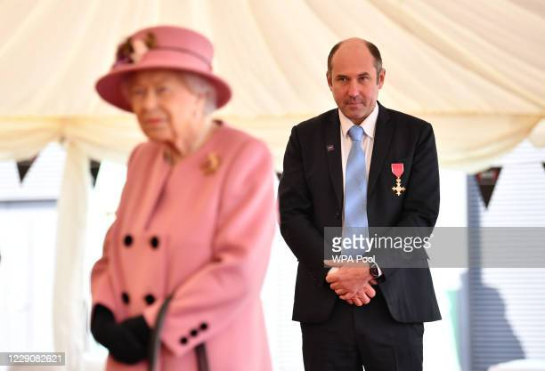 Britain's Queen Elizabeth II speaks with staff including Professor Tim Atkins who was honoured for his work on the 2018 Novichok incident and has...