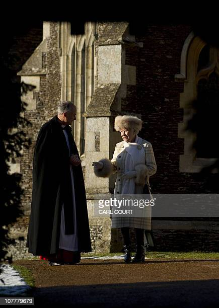 Britain's Queen Elizabeth II speaks with The Reverend Jonathan Riviere rector of Sandringham as she leaves after attending a Christmas Day church...