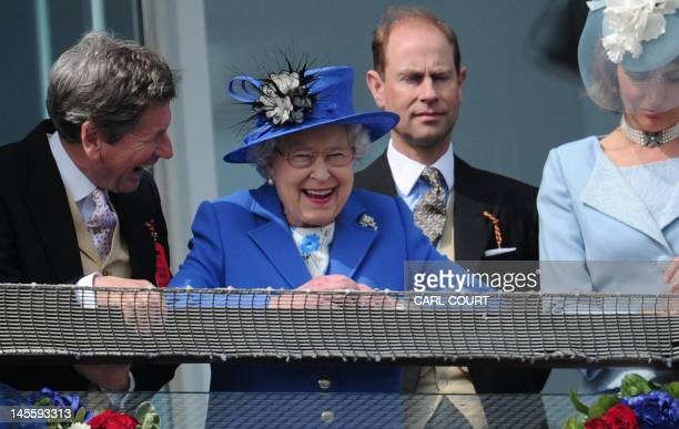 Britain's Queen Elizabeth II standing next to Prince Edward Earl of Wessex smiles from the royal balcony as she looks down on the winning horse in...