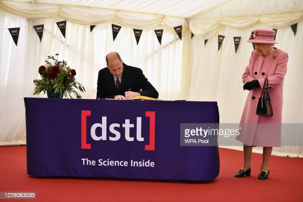 Britain's Queen Elizabeth II stands by as Prince William Duke of Cambridge signs a visitor's book during their visit to the Defence Science and...
