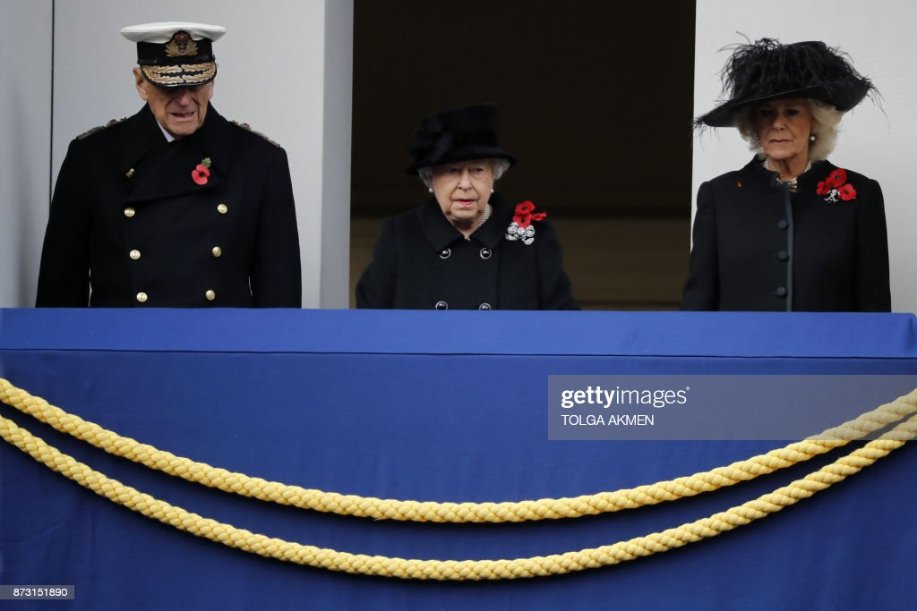 TOPSHOT - Britain's Queen Elizabeth II stands on the balcony with Britain's Prince Philip, Duke of Edinburgh and Britain's Camilla, Duchess of Cornwall during the Remembrance Sunday ceremony at the Cenotaph on Whitehall in central London, on November 12, 2017. Services are held annually across Commonwealth countries during Remembrance Day to commemorate servicemen and women who have fallen in the line of duty since World War I. / AFP PHOTO / Tolga AKMEN