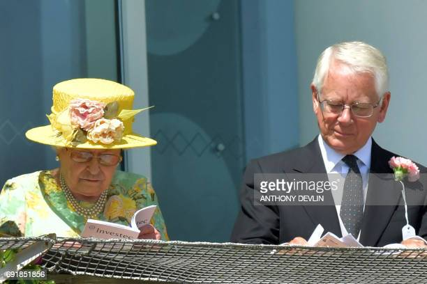 Britain's Queen Elizabeth II studies form on the second day of the Epsom Derby Festival in Surrey, southern England on June 3, 2017. / AFP PHOTO /...
