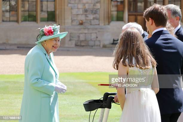 Britain's Queen Elizabeth II talks to 100-year-old veteran Captain Tom Moore and his family during an investiture to confer the honour of knighthood...