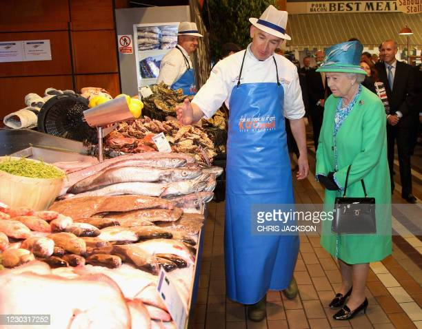 Britain's Queen Elizabeth II talks to fishmonger Pat O'Connell during a visit to the English market in Cork, on the last day of her four-day visit to...