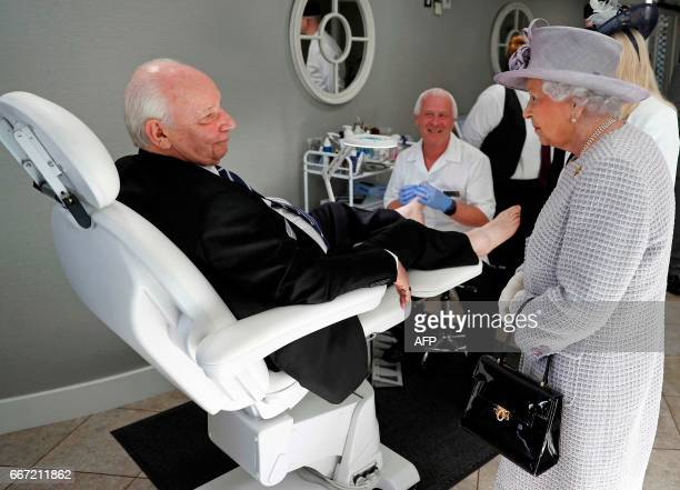 Britain's Queen Elizabeth II talks with a resident as he receives a treatment during her tour of Priory View an independent living scheme for older...