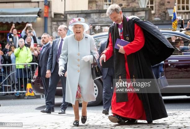 Britain's Queen Elizabeth II talks with Reverend Neil Gardner as she attends the Sunday Church service at Canongate Kirk in Edinburgh on June 30 2019