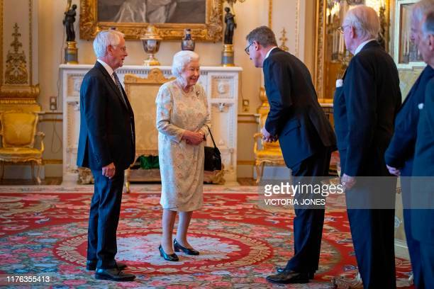 Britain's Queen Elizabeth II talks with trustees and staff from The Queen's Trust during a reception in Buckingham Palace London on October 17 to...