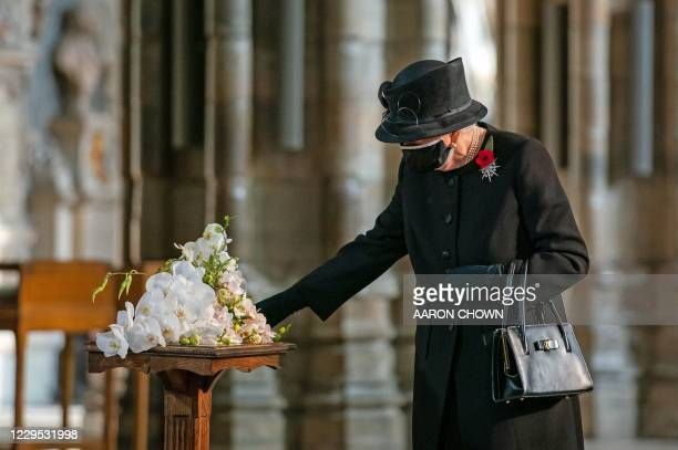Britain's Queen Elizabeth II touches a bouquet of flowers to be layed at the grave of the Unknown Warrior to mark the centenary of the burial of the...