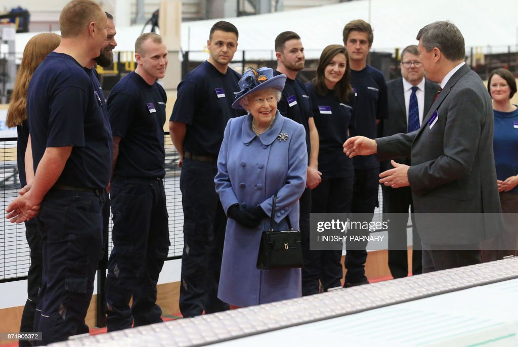 Britain's Queen Elizabeth II tours a blade production line with Managing Director of the Wind Power Division at Siemens, Clark MacFarlane (R) during her visit to the Siemens Gamesa Renewable Energy wind turbine blade factory in Kingston upon Hull, in northern England on November 16, 2017. / AFP PHOTO / POOL / Lindsey Parnaby