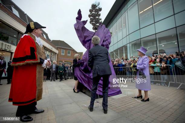 Britain's Queen Elizabeth II unveils a Diamond Jubilee monument to mark her 60 years on the throne watched by the local mayor Colin Rayner on October...
