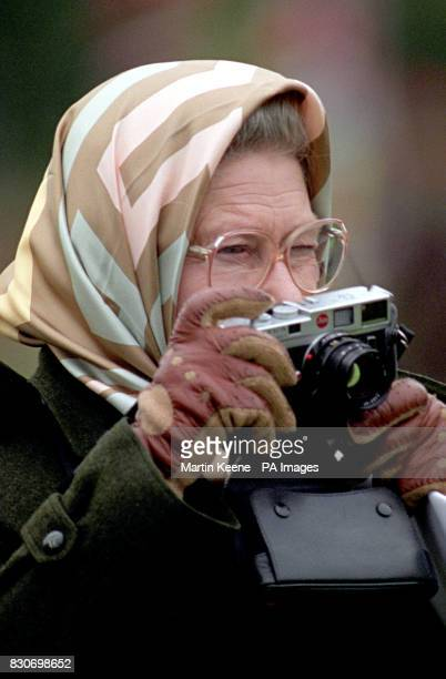 Britain's Queen Elizabeth II uses a Leica camera to take a photograph of her husband, the Duke of Edinburgh, as he competes in the Dressage Section...