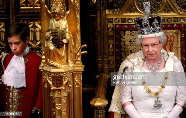 Britain's Queen Elizabeth II waits to deliver her speech as a page looks on in the House of Lords at the Palace of Westminster during the State...
