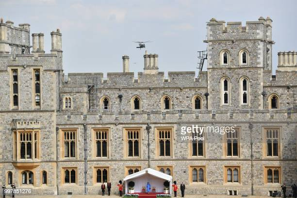 Britain's Queen Elizabeth II waits to greet US President Donald Trump as he arrives by helicopter at Windsor Castle on July 13 2018 in Windsor...