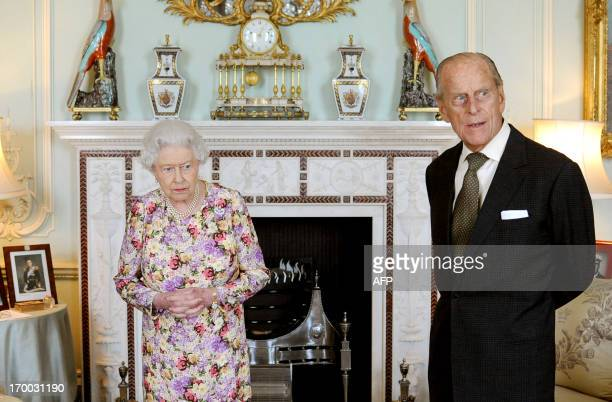 Britain's Queen Elizabeth II waits with Prince Philip Duke of Edinburgh before presented him with his medal and investing him with New Zealand's...