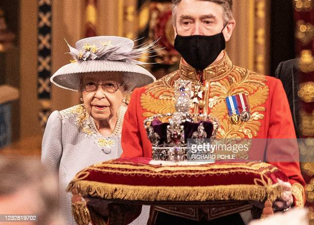 Britain's Queen Elizabeth II walks behind the Imperial State Crown as they process through the Royal Gallery, before delivering the Queen's Speech,...