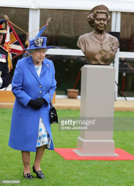 Britain's Queen Elizabeth II walks past a bronze bus of herself during a visit to the Honourable Artillery Company in London on June 1 2016 The...