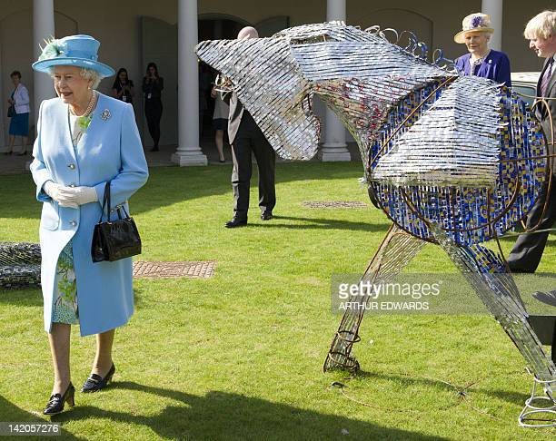 Britain's Queen Elizabeth II walks past a horse sculpture as she visits Valentines Park and Mansion in Redbridge, north London on March 29, 2012 for...