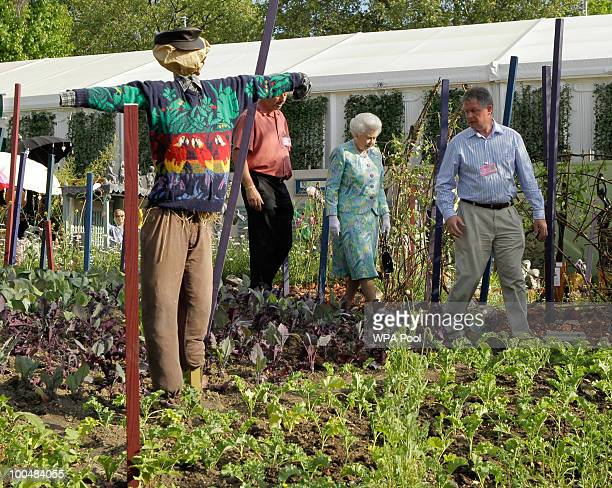 Britain's Queen Elizabeth II walks past a scarecrow as she visits a garden during the Press & VIP preview at The Chelsea Flower Show at Royal...