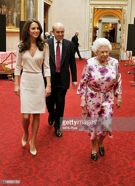 Britain's Queen Elizabeth II walks with Catherine Duchess of Cambridge as they view the exhibitions for the summer opening of Buckingham Palace on...