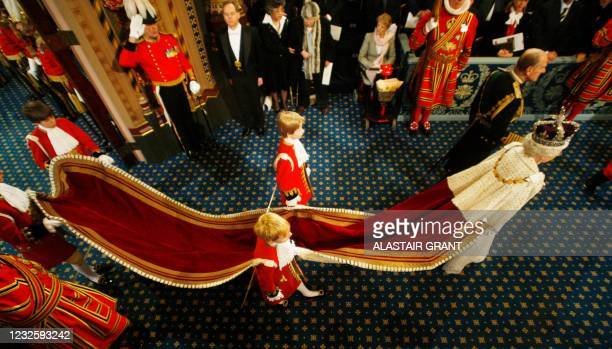 Britain's Queen Elizabeth II walks with Prince Philip in the Palace of Westminster, on her way to the House of Lords to make her annual speech for...