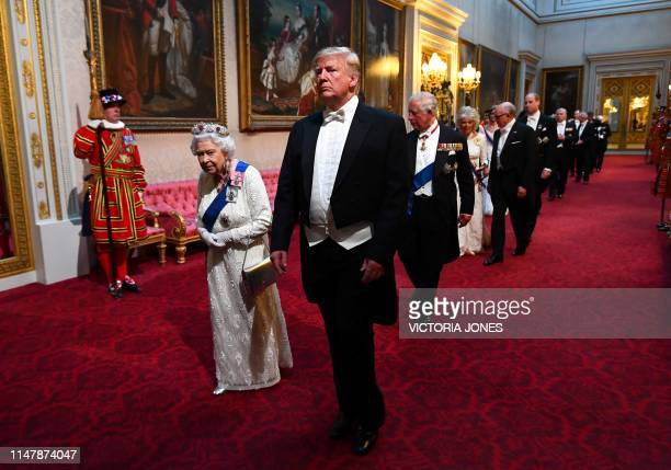 Britain's Queen Elizabeth II walks with US President Donald Trump and other guests as they arrive through the East Gallery during a State Banquet in...