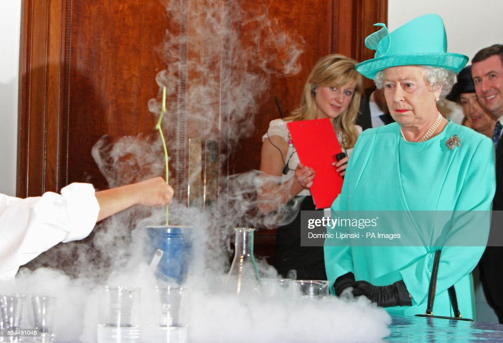 Britain's Queen Elizabeth II watches as a flower is immersed in liquid nitrogen as part of a science experiment at the Royal Institution of Great Britain, London.