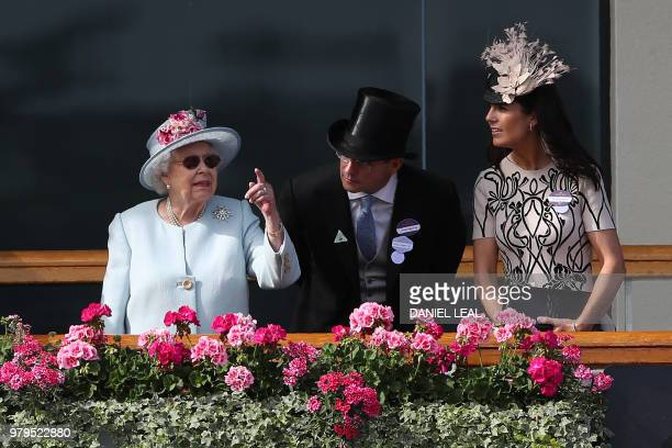 Britain's Queen Elizabeth II watches as jockeys and horses parade in the ring on the second day of the Royal Ascot horse racing meet in Ascot west of...