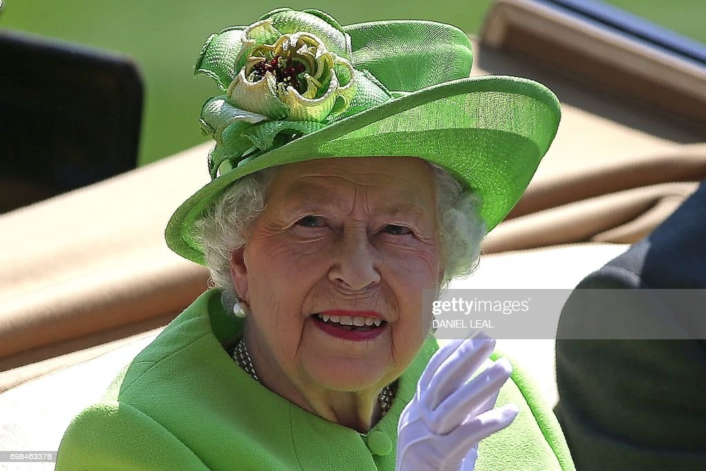 Britain's Queen Elizabeth II waves as she travels by horse-drawn carriage to arrive on day one of the Royal Ascot horse racing meet, in Ascot, west of London, on June 20, 2017. The five-day meeting is one of the highlights of the horse racing calendar. Horse racing has been held at the famous Berkshire course since 1711 and tradition is a hallmark of the meeting. Top hats and tails remain compulsory in parts of the course while a daily procession of horse-drawn carriages brings the Queen to the course. / AFP PHOTO / Daniel LEAL