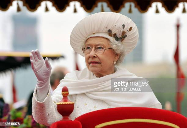 Britain's Queen Elizabeth II waves from the royal barge 'Spirit of Chartwell' as it sails past the Houses of Parliament during the Thames during the...