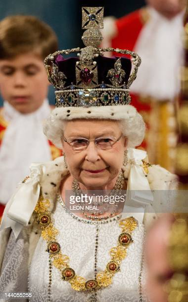 Britain's Queen Elizabeth II wearing the Imperial State Crown walks through the Royal Gallery toward the Chamber of the House of Lords in the Palace...