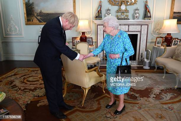 TOPSHOT Britain's Queen Elizabeth II welcomes newly elected leader of the Conservative party Boris Johnson during an audience in Buckingham Palace...
