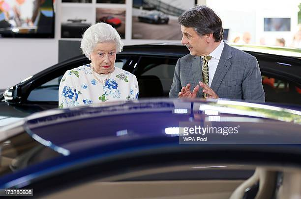 Britain's Queen Elizabeth looks at a Jaguar motor car on the first day of the Coronation Festival in the grounds of Buckingham Palace on July 11,...