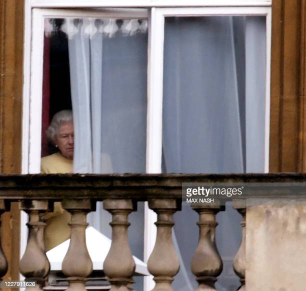 Britain's Queen Elizabeth looks out the window as the Honour Guard arrive in the courtyard of Buckingham Palace in London for King Harald of Norway's...