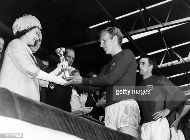 Britain's Queen Elizabeth of England presents the Jules Rimet Cup to Bobby Moore, captain of England's national soccer team, as her husband Prince...