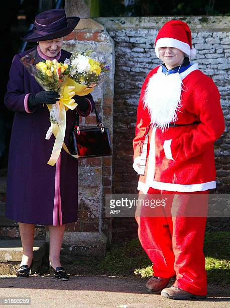 Britain's Queen Elizabeth receives flowers from a well-wisher dressed as Santa Claus outside St Mary Magdalene's church on the Sandringham estate...