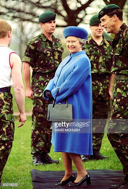 Britain's Queen Elizabeth shares a joke with recruits on the assault course 27 March during her visit to Devon at the Royal Marines Commando Training...