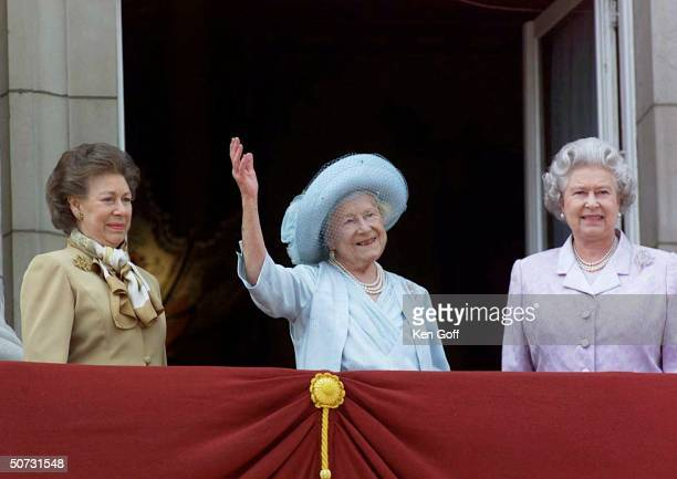 Britain's Queen Mother in blue hat and dress celebrating her 100th birthday w daughters Princess Margaret in brown and Queen Elizabeth II in lavender...